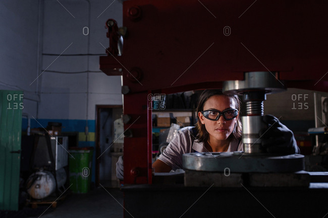 female mechanic operating hydraulic press