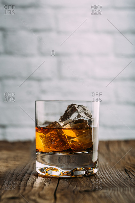 Glass of whiskey on a wooden table