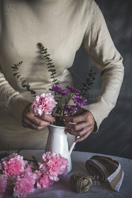 Graceful hands of the woman florist making bouquet of flowers on white table
