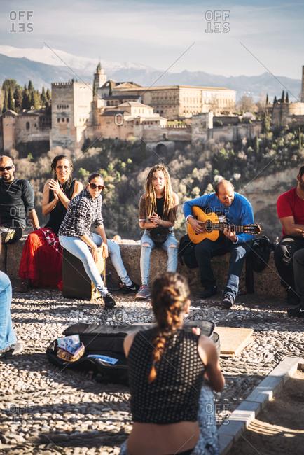 GRANADA, SPAIN - MARCH 07, 2017: Flamenco musicians sitting in patio against Alhambra fortress, Granada, Spain,