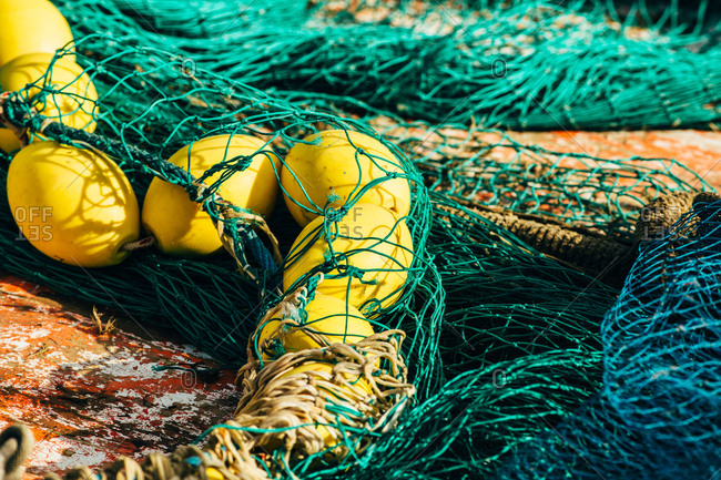 Green fishing net with yellow floats in Palamos, Spain, Horizontal outdoors shot,