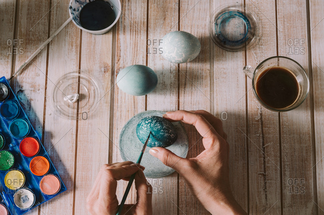 Hands of person painting the egg decoration for easter, Horizontal indoors shot,