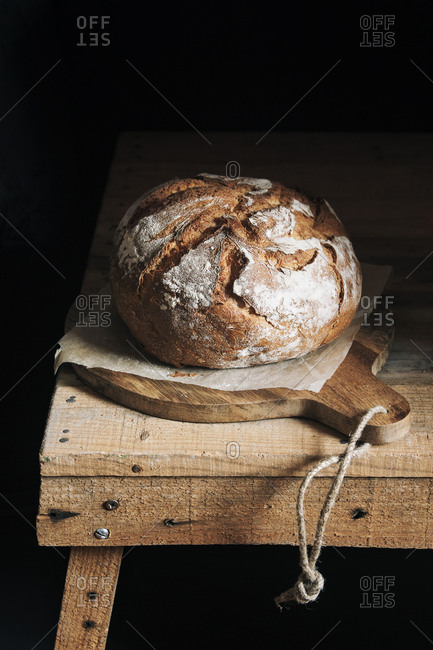 Homemade bread on cutting board and dark background