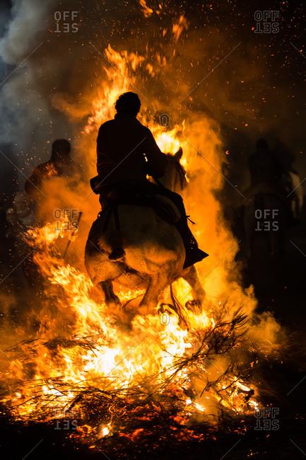 Horse riding through bonfire in a purification ritual