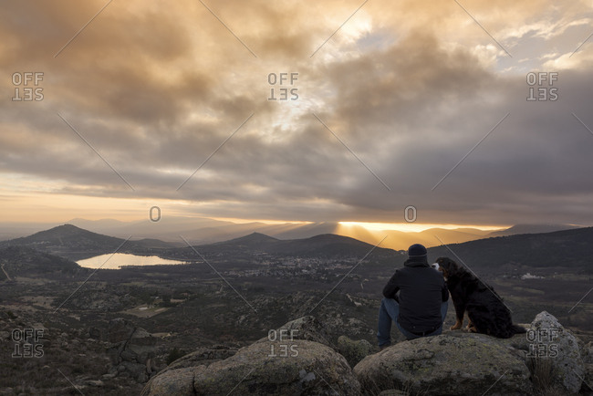 Man and his pet contemplate the sunset from the top of the mountain