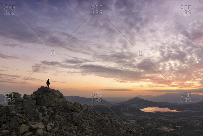 Man contemplate the sunset from the top of the mountain