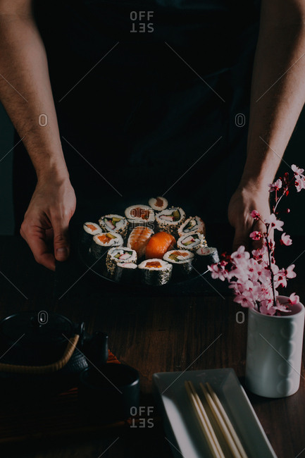 Man holding some sushi served on blackboard with wooden table on the background and flowers as decoration