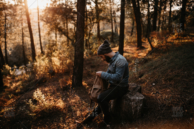 Man in forest looking into backpack