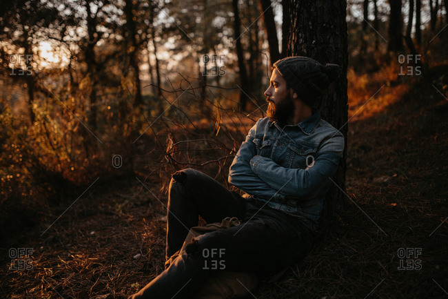 Man sitting at the tree in forest and looking at sunset, Horizontal outdoors shot,