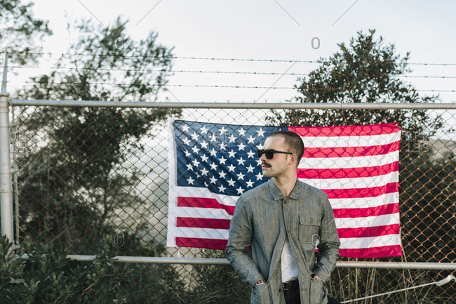 Man wearing sunglasses standing at the chain wire wall with the USA flag, Horizontal outdoors shot,