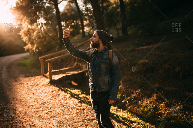 Man taking selfie on sunny autumn road