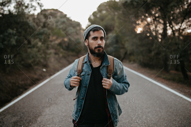 Man with backpack standing on a road, Horizontal outdoors shot,