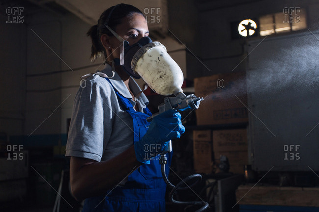 Woman holding a paint spray gun