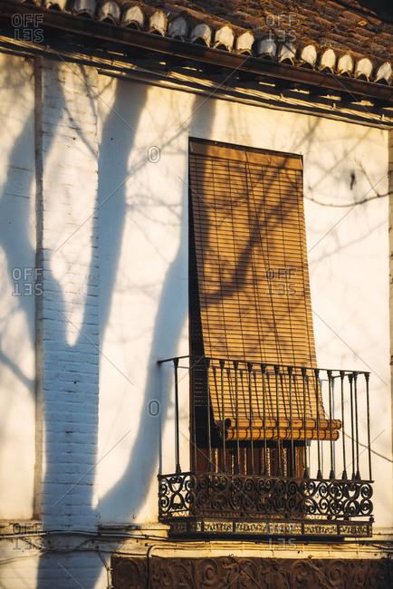 Metal balcony with door shuttered down in sun light, Granada, Spain,