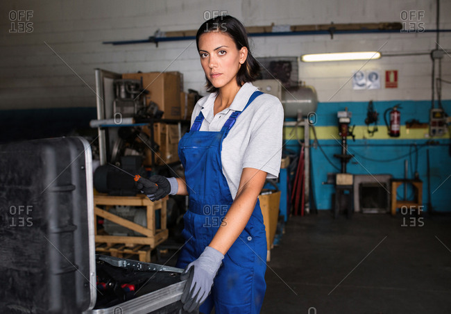 portrait of a female mechanic  in a garage  looking at camera