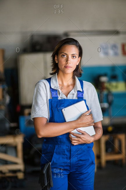 portrait of a female mechanic  in a garage  looking at camera and holding a tablet computer
