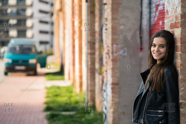 Portrait of young smiling woman standing at the brick wall,