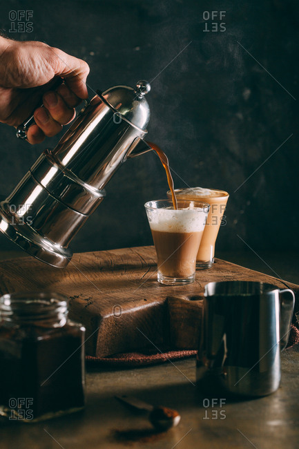 Pouring hot coffee into a glass on dark background