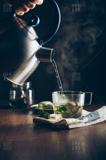 Pouring hot water into a cup of tea on dark background