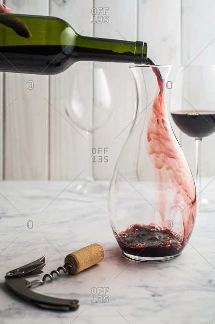 Pouring red wine from a bottle to a decanter