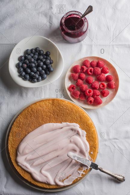 Preparing berries cake with yogurt frosting