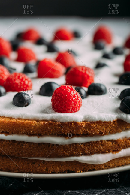 Preparing berries cake with yogurt frosting