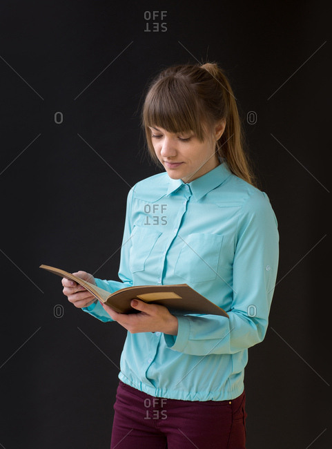 Pretty young woman reading a book standing on the black background, Vertical studio shot,