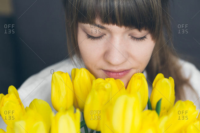 Pretty young woman sniffing the yellow colored tulips with the eyes closed, Horizontal studio shot,
