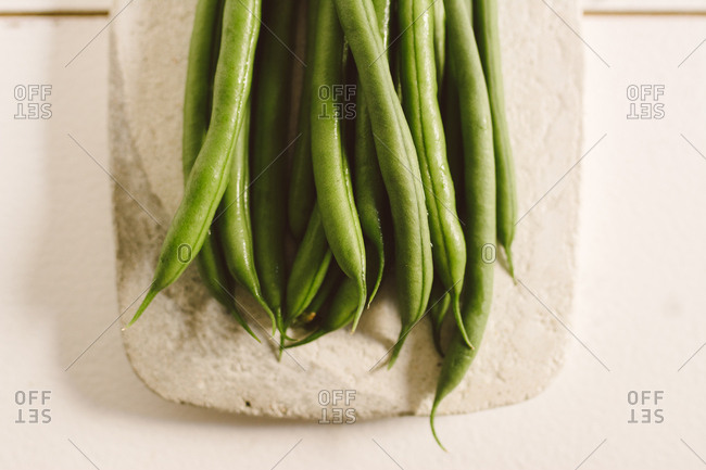 Raw round green beans on stone table, from above