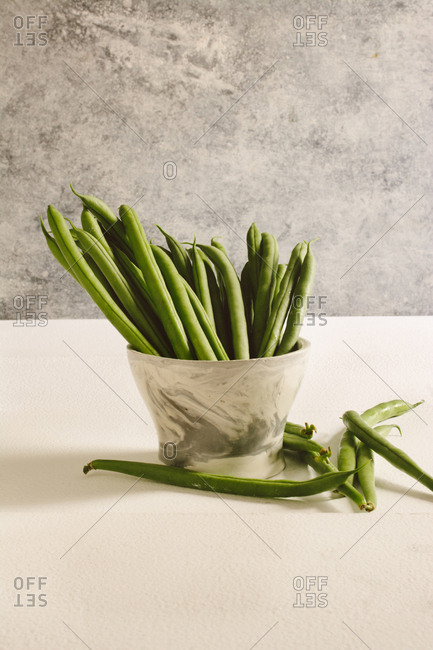 Raw round green beans, on marble bowl