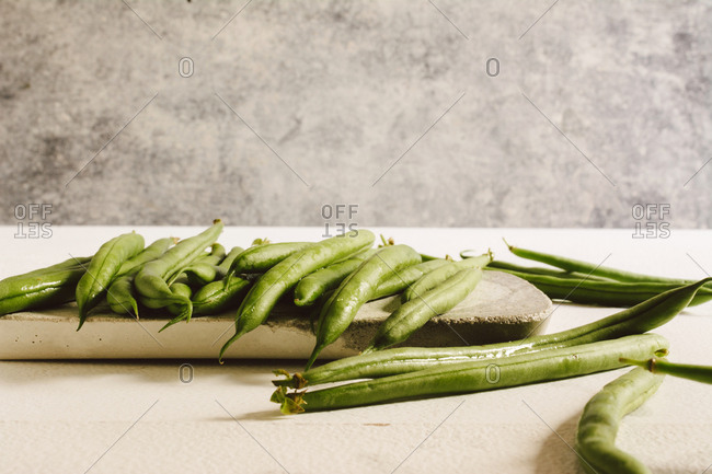 Raw round green beans, on stone table