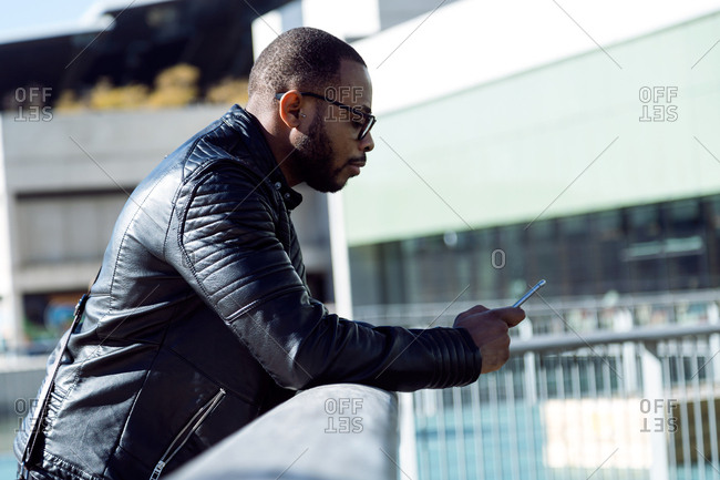 Side view of young male in leather black jacket bending on metal fence and using phone,