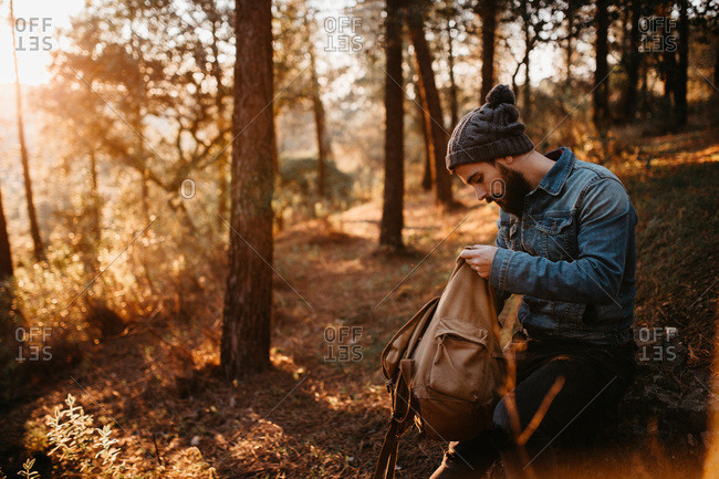 Side view of young tourist looking into backpack in the autumn forest, Horizontal outdoors shot,