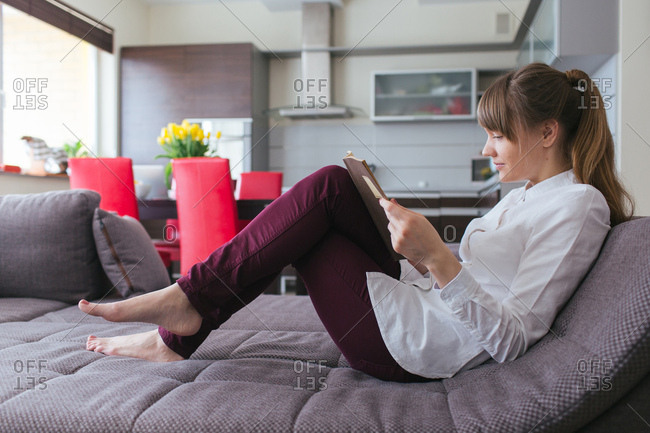 Smiling woman with the book on a sofa, Horizontal indoors shot,