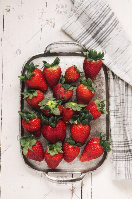 Strawberries in spring on silver plate over white wooden
