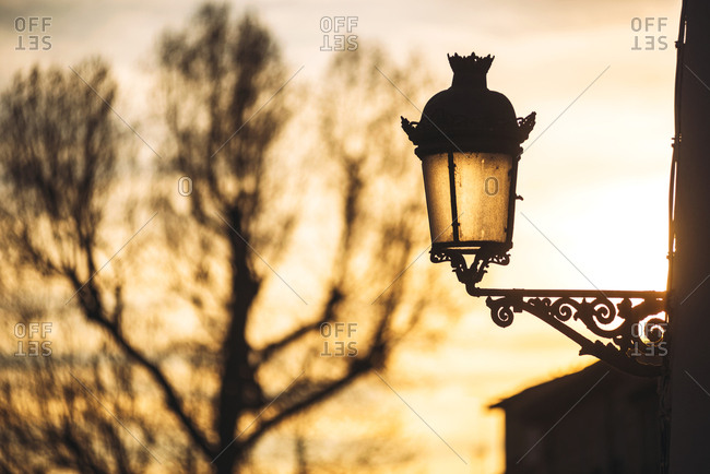 Street metal lantern hanging on wall in sunset light, Granada, Spain,