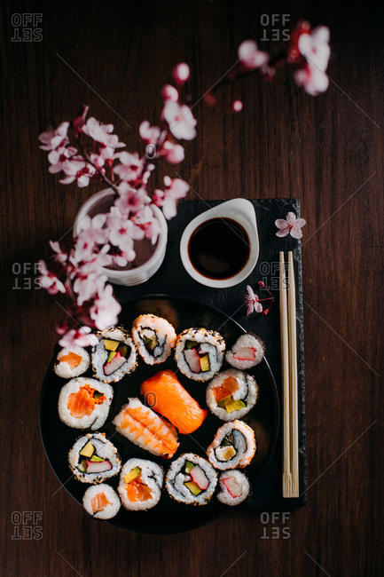 Sushi served on blackboard with wooden table on the background and flowers as decoration