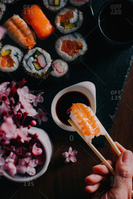 Sushi served on blackboard with wooden table on the background and flowers as decoration and one hand picking a piece of sushi