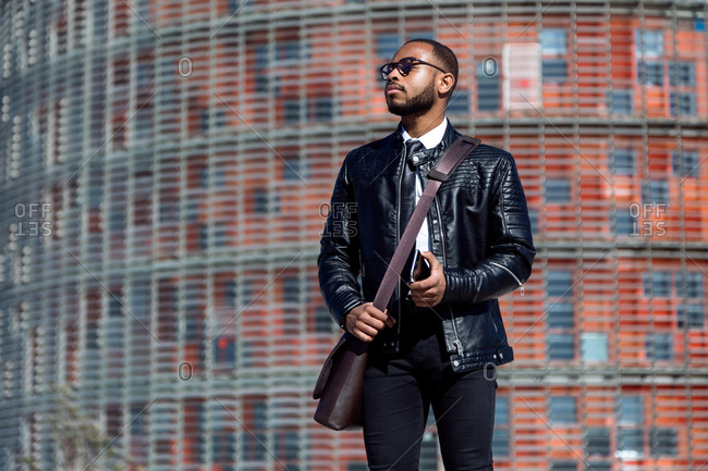 Trendy man in black leather coat and glasses holding smart phone and looking away on urban background,