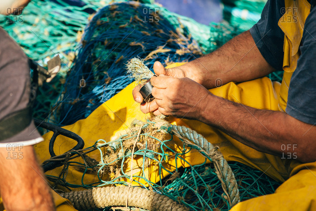 Unrecognizable person in yellow uniform with fishing net in Palamos, Spain, Horizontal outdoors shot,