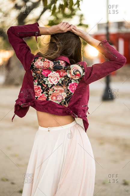 Vertical back view of stylish young woman posing outside,
