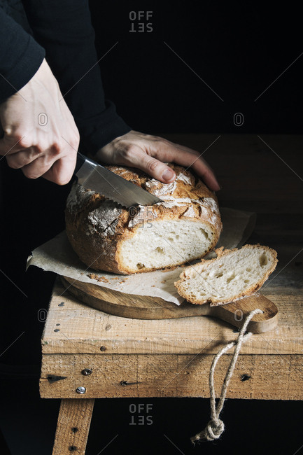 Woman cutting homemade bread with dark background