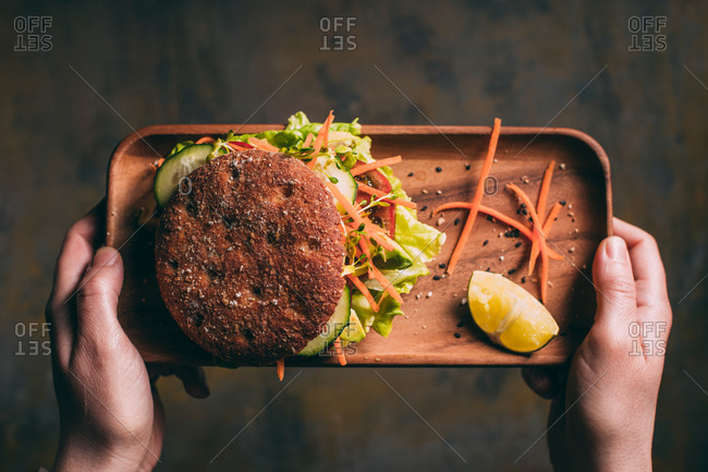 Woman holding a tray with a vegetarian sandwich with lettuce, cucumber, carrot tomato and avocado