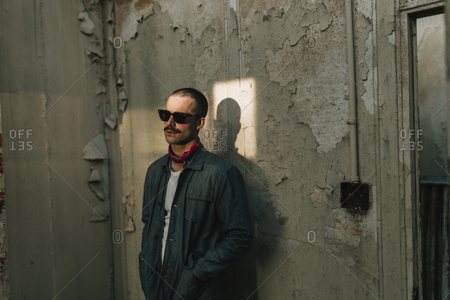 Young confident man wearing sunglasses standing at the old rough wall, Horizontal indoors shot,