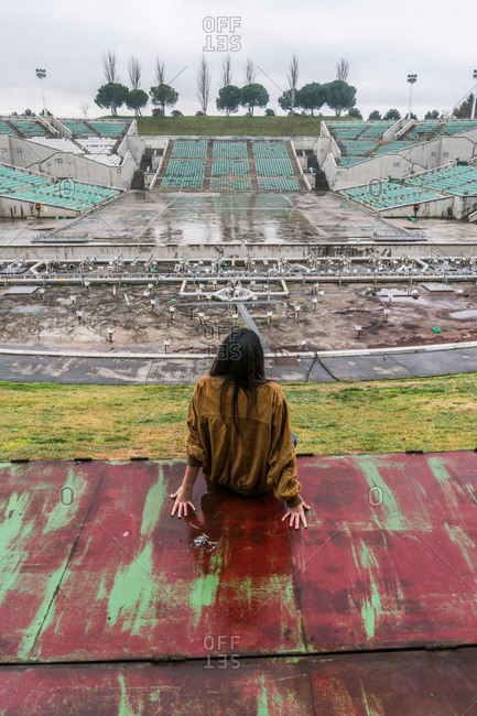 Young cute girl in an abandoned stadium