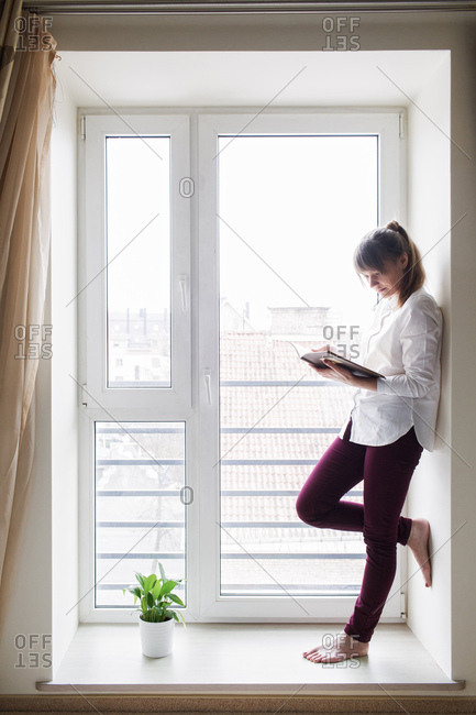 Young female standing on a window and reading a book, Vertical indoors shot,