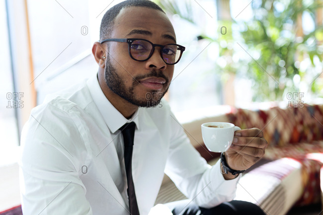 Young handsome male in formal outfit and glasses holding cup of coffee and looking at camera,