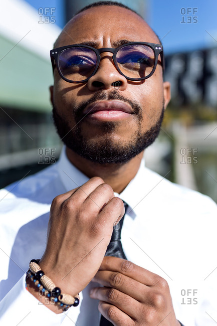 Young handsome man in glasses wearing white shirt and setting black tie on blurred urban background,