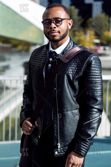 Young handsome successful male in leather jacket and with bag over shoulder posing confidently and looking at camera,