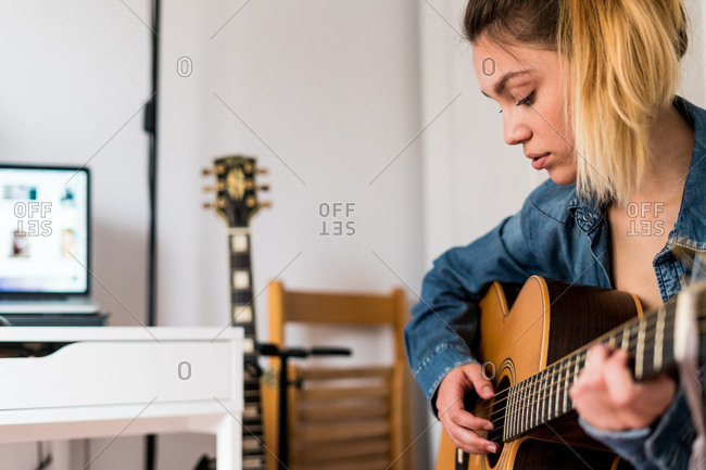 Young pretty female musician playing an acoustic guitar in her apartment,